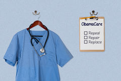 Blue scrubs shirt for medical professional hanging with clipboar Royalty Free Stock Images