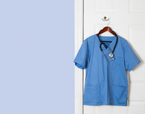 Blue scrubs shirt for medical professional hanging on door. Blue medical scrubs uniform shirt hanging on a hook on back of door with stethoscope with copy space stock photography