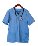 Blue scrubs shirt for medical professional hanging isolated. Blue medical scrubs uniform shirt hanging on a hanger with stethoscope and isolated against white Stock Image