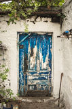 Blue scuffed timber door of the white house Royalty Free Stock Image