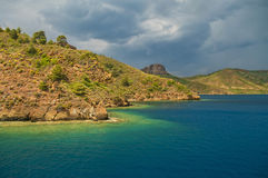 Blue sea around sunlit rocky islands on stormy day Royalty Free Stock Image