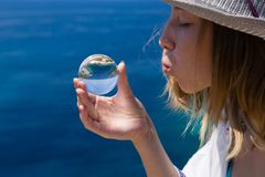 Beautiful young lady with glass ball. Face, hand, natural outdoors scene. Blue sea background. stock photo