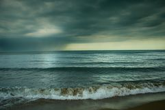 Blue sea with black clouds Stock Photo
