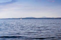Blue sea, blue sky and white sailing boat Stock Photos