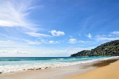 Blue sea. Clear sky. Green Mountain. Wet sand. White clouds Stock Photography