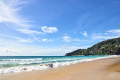Blue sea. Clear sky. Green Mountain. Wet sand. White clouds Royalty Free Stock Images