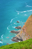 Blue Sea and Cliffs. Looking down over cliffs to a rocky foreshore and the deep blue ocean royalty free stock photo