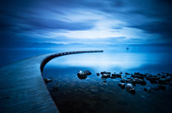 Blue sea and curve jetty Stock Image