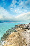 Blue sea and detailed ground coast with cloudy sky. In blue color. there are rocks on the sea side with clear water under the busy white clouds Royalty Free Stock Image