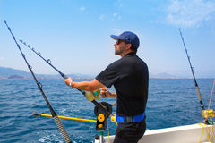 Blue sea fisherman in trolling boat with downrigger. Blue sea fisherman in trolling boat in action with downrigger and rod Stock Image