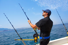 Blue sea fisherman in trolling boat with downrigger. Blue sea fisherman in trolling boat in action with downrigger and rod Stock Photos