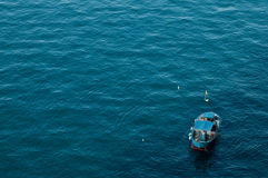 Blue sea and fishing boat Stock Image