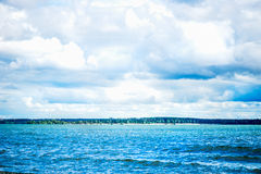 Blue Sea Front, Cloudy Sky, Sandy Beach and City on the Backgrou Stock Photo