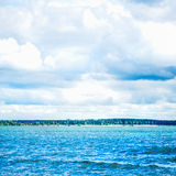 Blue Sea Front, Cloudy Sky, Sandy Beach and City on the Backgrou Stock Photography