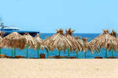 Blue sea, golden sand and sunbeds on the beach Royalty Free Stock Photo