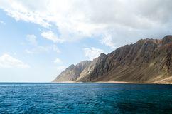 Blue sea and high rocky mountains against the sky and clouds in Egypt Dahab South Sinai royalty free stock photos