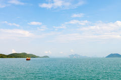 Blue sea lagoon with limestone green islands, cloudy sky and a w. Ooden boat in clean calm blue water Stock Photography