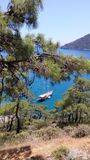 Blue sea laguna with yacht and pines trees at foreground. Adrasan Beach Turkey stock photo
