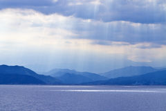 Blue sea, mountains & clouds in sky Royalty Free Stock Photography