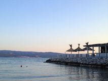Beach in Omis, Croatia at sunset. Blue sea, mountains and sky, beach bar at right with three straw umbrellas royalty free stock images