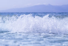 Blue sea or ocean, beautiful waves, drops, sky, mountains Royalty Free Stock Image