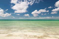 Blue sea or ocean, white sand and sky with clouds Royalty Free Stock Image