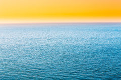 Blue Sea Or Ocean And Yellow Clear Sunset Or Sunrise Sky Background Stock Photo