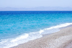 Blue sea with pebble beach Royalty Free Stock Photos
