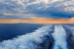 Blue sea with prop wash wake in Ibiza Island. Blue sea with prop wash wake and Ibiza Island in horizon on sunrise stock images