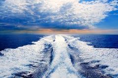 Blue sea with prop wash wake in Ibiza Island. Blue sea with prop wash wake and Ibiza Island in horizon on sunrise stock photos