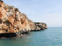 Blue sea and red rocks with caves. Red cliffs rise above the blue sea on The East Coast of Majorca Island. The sea waves have dug picturesque caves in the rocks Royalty Free Stock Image