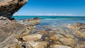 Blue sea and rocks in the front. Rocky coastline with some blue sky and clear water. big stones royalty free stock photos