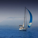 Blue sea with sailboat sailing in a foggy coast Stock Images