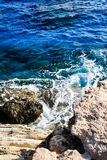In the blue sea sailing white yacht. Seawater waves hit the rocks and forms a foam. Cyprus Royalty Free Stock Photography
