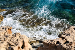 In the blue sea sailing white yacht. Seawater waves hit the rocks and forms a foam. Cyprus Stock Images