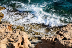 In the blue sea sailing white yacht. Seawater waves hit the rocks and forms a foam. Cyprus Royalty Free Stock Photo