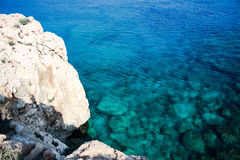 In the blue sea sailing white yacht. Seawater waves hit the rocks and forms a foam. Cyprus Stock Photo