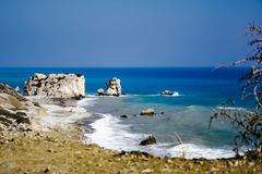 In the blue sea sailing white yacht. Seawater waves hit the rocks and forms a foam. Cyprus Stock Image