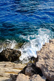 In the blue sea sailing white yacht. Seawater waves hit the rocks and forms a foam. Cyprus Royalty Free Stock Images