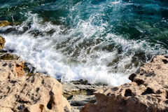 In the blue sea sailing white yacht. Seawater waves hit the rocks and forms a foam. Cyprus Stock Photography