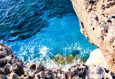 In the blue sea sailing white yacht. Seawater waves hit the rocks and forms a foam. Cyprus Stock Photos