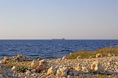 Blue sea and ship. The ship is far away in the sea. stock image
