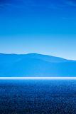 Blue sea and sky with distant mountains Royalty Free Stock Photography
