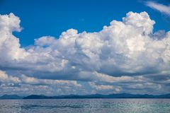 Blue sea and sky landscape with distant island. Romantic tropical cloudscape with green island photo background. Philippines marine view. Exotic island hopping stock images