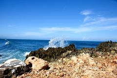 Blue sea and blue sky. Blue sky over the bue sea with a wave breaking on the rocks. peaceful moment stock photos