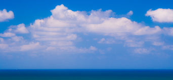 Blue sea and sky. A view across the surface of blue seas with blue skies and white clouds above Stock Images