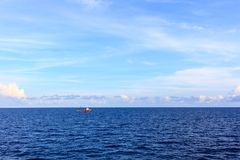 Blue sea and blue sky with white cloud and supply boat sailling. In background Royalty Free Stock Image