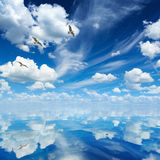 Blue sea and sky, white clouds, sunny weather, three seagulls fl. Peaceful heavenly background - blue sea and sky, white clouds, sunny weather, three seagulls Royalty Free Stock Photography