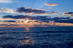 Blue sea with sun rays of sunset Royalty Free Stock Image