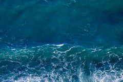 Blue sea texture with waves and foam stock photos